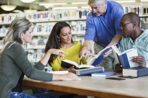 Graduate school or continuing education:  multi-ethnic group of adult students meeting and studying together in the library.  Mixed ages, 20s to 50s.